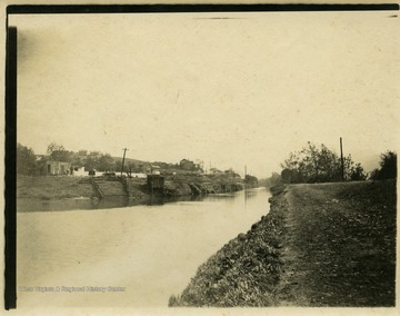 This image is part of the Thompson Family of Canaan Valley Collection. The Thompson family played a large role in the timber industry of Tucker County during the 1800s, and later prospered in the region as farmers, business owners, and prominent members of the Canaan Valley community.The image shows a view of the Cumberland Canal in Cumberland, Md.