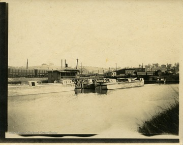 This image is part of the Thompson Family of Canaan Valley Collection. The Thompson family played a large role in the timber industry of Tucker County during the 1800s, and later prospered in the region as farmers, business owners, and prominent members of the Canaan Valley community.The image shows canal boats and a train in the background.