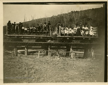This image is part of the Thompson Family of Canaan Valley Collection. The Thompson family played a large role in the timber industry of Tucker County during the 1800s, and later prospered in the region as farmers, business owners, and prominent members of the Canaan Valley community.Large group of unidentified people, men in left car and women in the right car, pose in train cars while taking the railroad to Blackwater Falls for a picnic.