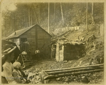 "This image is part of the Thompson Family of Canaan Valley Collection. The Thompson family played a large role in the timber industry of Tucker County during the 1800s, and later prospered in the region as farmers, business owners, and prominent members of the Canaan Valley community.Men and women are seen throughout the camp.Caption on back of photo reads: ""Possibly Bob Eastman?"""