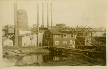 This image is part of the Thompson Family of Canaan Valley Collection. The Thompson family played a large role in the timber industry of Tucker County during the 1800s, and later prospered in the region as farmers, business owners, and prominent members of the Canaan Valley community.A partially burned mill including the boiler and burner are damaged.