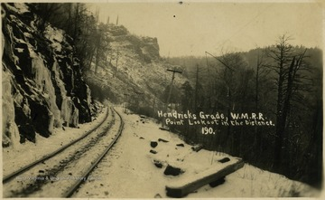 A snowy view of Hendricks Grade on the W.M.R.R. with Point Lookout in the distance.This image is part of the Thompson Family of Canaan Valley Collection. The Thompson family played a large role in the timber industry of Tucker County during the 1800s, and later prospered in the region as farmers, business owners, and prominent members of the Canaan Valley community.