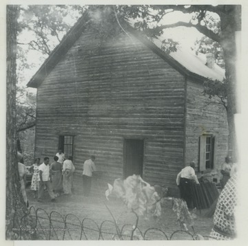 A group of church goers are gathered outside of the church, which was established in the Rock Gap District in 1797. The chapel had a greater influence on rural religion and in the spread of the German Evangelical movement than any other in Morgan County, W. Va. For years, the German preachers of the United Brethren shared the chapel with English Methodist preachers, often conducting services in both the English and German languages.