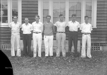 Seven unidentified men pose together.