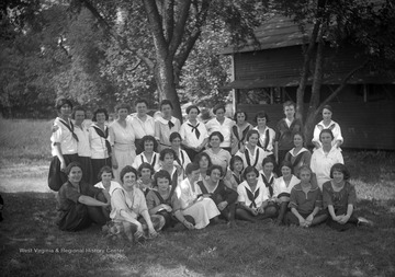 A group of unidentified women pose outside of a 4-H camp.