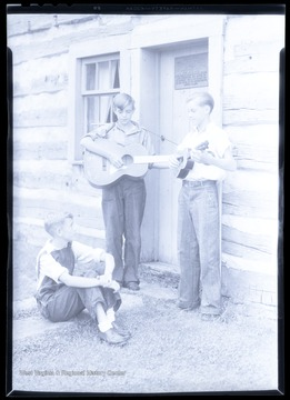 A boy watches as his two companions play their string instruments. Subjects unidentified.