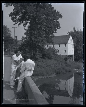 Two unidentified boys look out over the water beside the historic building.