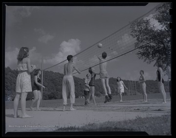 Unidentified teens play a game of volleyball in an unidentified location.