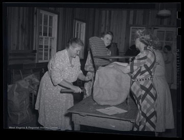"Four unidentified women assemble a chair together. The photo labels the location as the ""R. E. Building."""