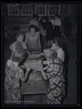 "A group of unidentified women work together to assemble a chair. The photo describes this location as the ""R. E. Building."""