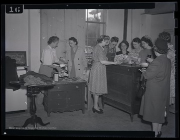 "A group of women learn how to finish furniture properly. The photograph description identifies the location as the ""R. E. Building."""