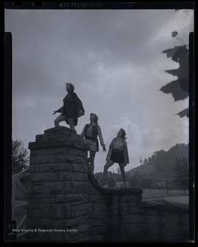 Three unidentified girls pose on top of the stone fence.