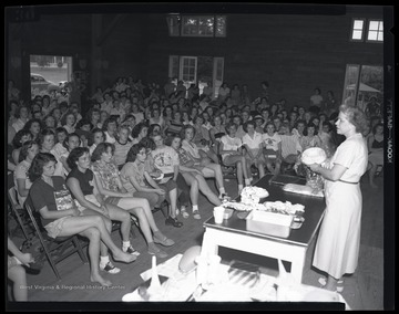 A group of young, female campers listen as an instructor speaks about frozen food. Subjects unidentified.