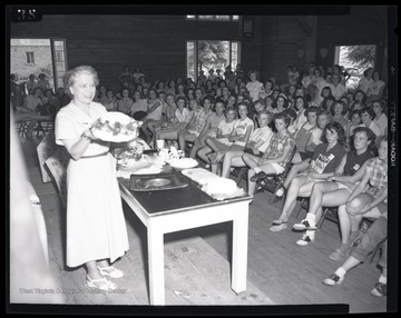 An unidentified woman speaks to a group of young girls as she holds up what appears to be a cake.