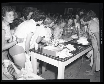 A group of unidentified girls inspect the desserts left on the table.