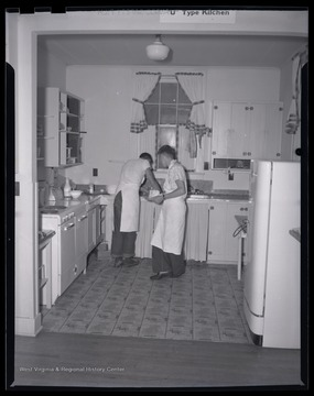 Two unidentified boys work together in the kitchen.