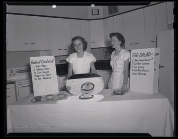 Two unidentified women show female campers how to correctly bake custard.