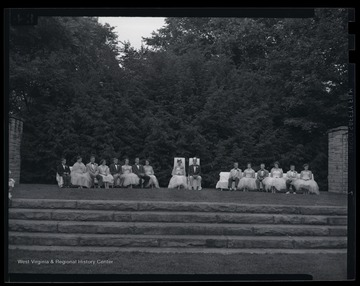 The royal court is pictured on a lawn stage. Subjects unidentified.