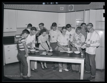 A group of unidentified boys participate in kitchen activities.