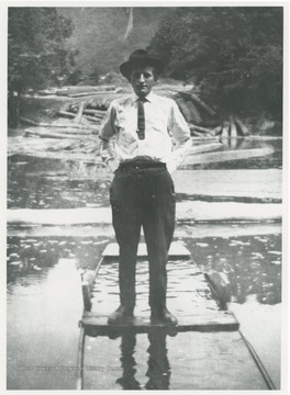 Portrait of a man standing in a flooded boat, possibly the photographer, Robert Keller.