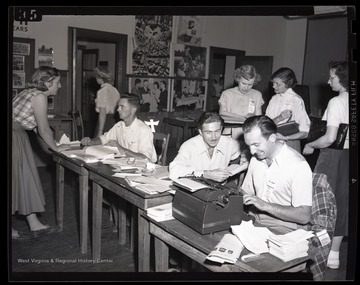 A group of young men and women working. Subjects unidentified.