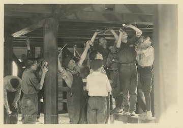 A group of young men and boys place electrical wiring along wooden beams. Subjects unidentified.  Subjects are likely members of a 4-H organization.