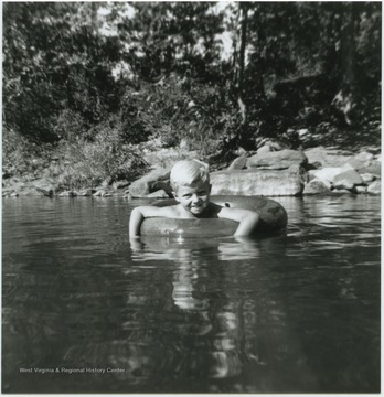A young, unidentified boy floats in a tube in what is also known as Greenbrier Springs. The springs are located along the Greenbrier River.