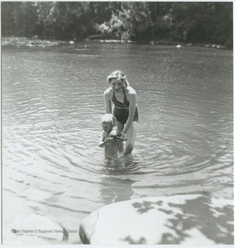 A young woman holds her son up in the water. Barger Springs, also known as Greenbrier Springs, is located along the Greenbrier River.
