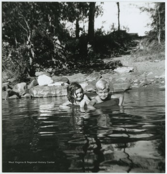 A boy and girl share an inner tube while floating in the waters, also known as Greenbrier Springs, which is located off of the Greenbrier River. Subjects unidentified.