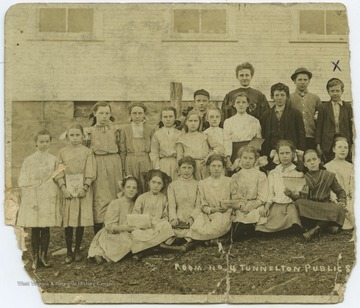 "The students of classroom no. 4 pose together for a class photo outside of the school building. C. Paul Miller is marked on the photo with an ""x"" above his head."