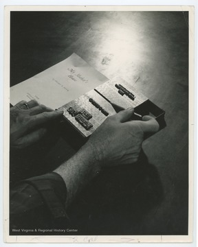 "An unidentified man sets the type for the title page of ""My Mother's House"", a short story by Pearl S. Buck."