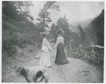 Mrs. Ro. Murrell and another woman walk down a dirt road.