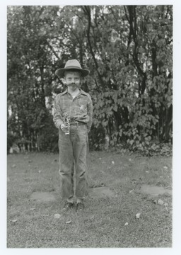 Miller Murrell dressed as sheriff or police officer with false mustache, badge, and toy gun. Location near Hinton, W. Va.