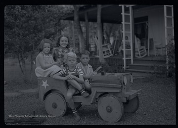 Miller Murrell, in a striped shirt, and three friends sit in a wooden jeep.  Behind them is a large porch with several adults sitting.  A large toy gun sits on the ground.