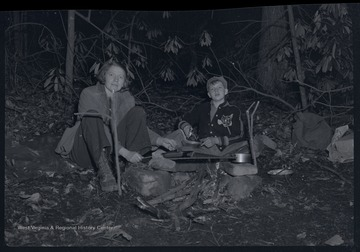 Miller Murrell and his mother cook with several pots and pans over a fire.  They appear to be camping outdoors.