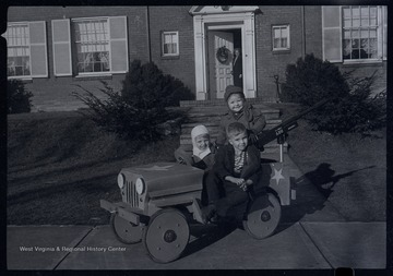 Miller Murrell and two other children sit in front of a house, likely on or near Ballengee Street in Hinton, W. Va.  The children are in a wooden jeep.  A large toy gun is mounted on the rear of the vehicle.