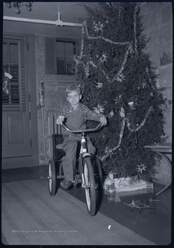 Miller Murrell on a bike next to the family Christmas tree in the basement of their home at 309 Ballengee Street, Hinton, W. Va.