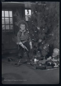Miller Murrell dressed as a sheriff next to a Christmas tree.  He is in the basement of the Murrell family home at 309 Ballengee Street, Hinton, W. Va.