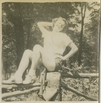 Davis is pictured sitting on top of a wooden fence.