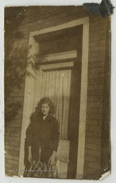 An unidentified female student stands outside of a building.
