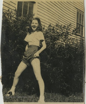 An unidentified female student poses on a lawn.