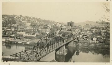 View of downtown Morgantown from across the Monongahela River bridge.  Several buildings have visible company names painted onto them.