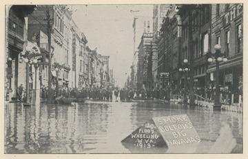 "Photo postcard of a crowd of people on Market Street in Wheeling, W. Va. during a 1913 flood. Several business signs are visible, including a sign which reads ""Smoke Bolton's Big Havanas."" Postcard is part of a souvenir book of 1913 flood images."