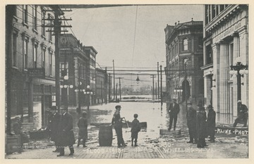 Photo postcard showing 18th Street during the 1913 flood in Wheeling, W. Va. Postcard is part of a souvenir book of 1913 flood images.