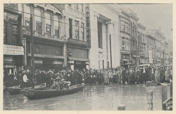 Photo postcard of Market Street above 14th Street during a 1913 flood in Wheeling, W. Va. Several business signs are visible including Bolton's, Kraus Brothers, and C.A. House Pianos. Postcard is part of a souvenir book of 1913 flood images.