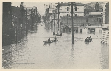 Photo postcard of an unidentified intersection in Wheeling, W. Va., likely Market Street or nearby. Several business signs are visible. Postcard is part of a souvenir book of 1913 flood images.