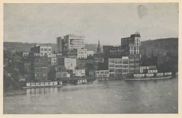 Photo postcard of the Wheeling waterfront during a flood.  Several buildings and business signs are visible, including the Schmulbach building, Uneeda Biscuit, The Home Outfitting Co., Chew Mail Pouch Tobacco, and others. Postcard is part of a souvenir book of 1913 flood images.