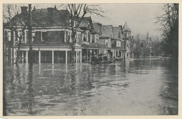 Photo postcard of unidentified homes during a 1913 flood.  Two boats are visible floating on the flooded streets.  Postcard is part of a souvenir book of 1913 flood images.