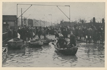 Photo postcard of a flooded street in Wheeling, W. Va. during a 1913 flood.  Several boats float in the flooded part of the street while crowds gather on dry sections. Postcard is part of a souvenir book of 1913 flood images.