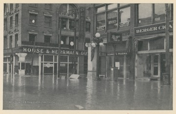 Photo postcard of 14th and Market Streets during a 1913 flood in Wheeling, W. Va.  The House & Hermann department store building is visible, as are other businesses and signs. Postcard is part of a souvenir book of 1913 flood images.